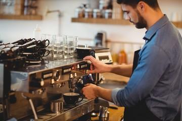Man taking coffee from espresso machine