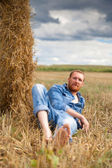bearded man on   field at harvest time.
