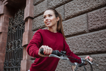 Young woman dressed in sweater walking with her bicycle