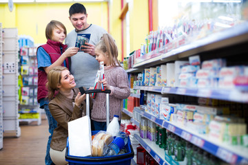 Family buying tooth-brush in supermarket.