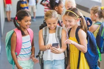 School kids using mobile phone in corridor