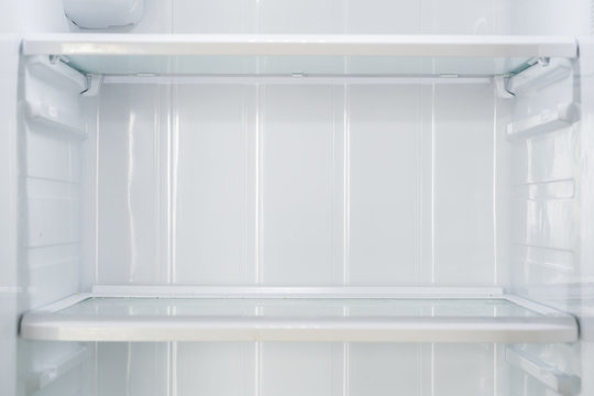 Empty open fridge with shelves, refrigerator.