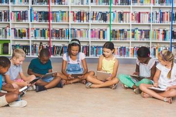 School kids sitting on floor using digital tablet in library