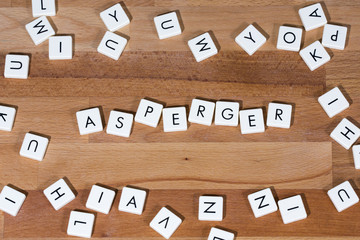Asperger text on a wooden surface surrounded by letters. Asperger Syndrome is a neurobiological disorder on the higher-functioning end of the autism spectrum.