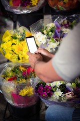Male florist taking photo of flower bouquet