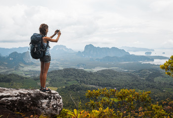 Young lady hiker with backpack standing on top of the mountain and taking a picture of valley
