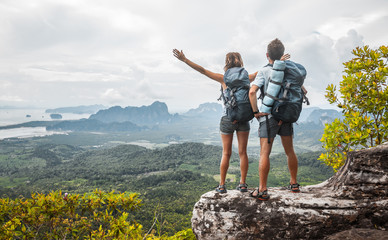 Hikers with backpacks relaxing on top of a mountain and enjoying the view of valley Wall mural