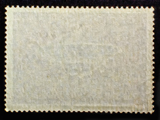 Old posted stamp reverse  side with the edge of the sheet. Texture of paper.