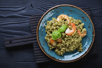 Spinach and tiger shrimps risotto on a black wooden background