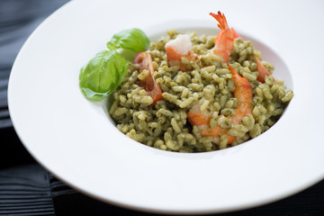 Risotto with spinach, tiger shrimps and tomatoes, close-up
