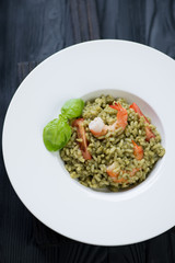 Spinach and tiger shrimps risotto in a white plate, top view