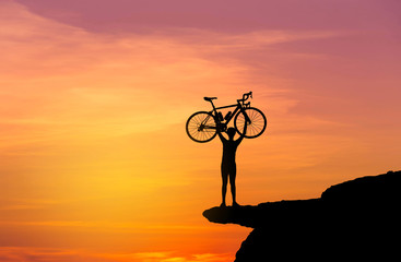 Silhouette the man in action lifting bicycle above his head stand on top of the rock cliff mountain with sunset twilight background.