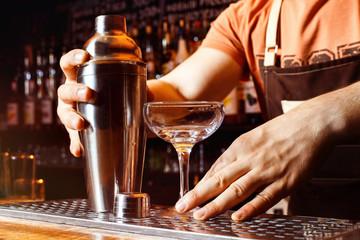 bartender is making cocktail holding shaker at bar background