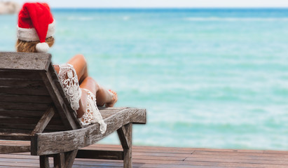 Young woman in santa claus hat celebrating Christmas sitting in chaise lounge on tropical sea beach