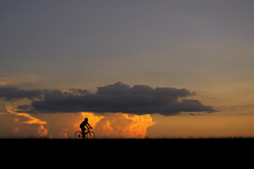 Silhouette image of a cyclist (young man or woman) on the road with sunset and clouds in the background
