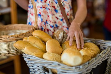 Mid section of woman selecting bread