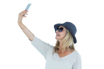 Woman taking selfie against white background