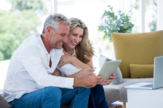 Smart mature couple using digital tablet