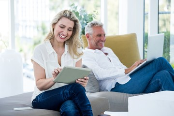 Smiling mature couple using technology