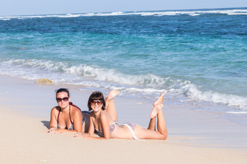 Portrait of two young female friends lie on the sea shore looking at camera and laughing. Caucasian young women strolling along a beach. Tropical island Bali, Indonesia.