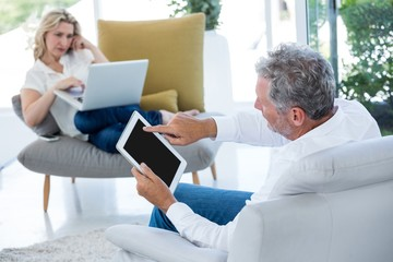 Man using tablet while woman holding laptop