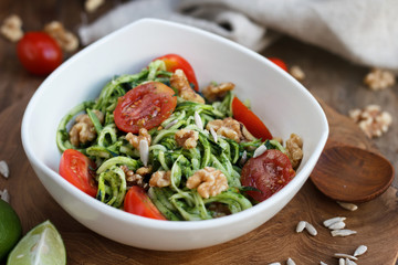 Raw zucchini pasta with tomatoes and walnut with pesto in white bowl