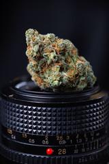 Dried cannabis bud in top of digital camera lens - marijuana pho