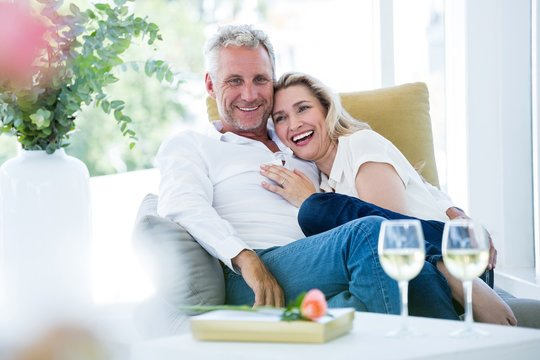 Happy romantic mature couple sitting on armchair