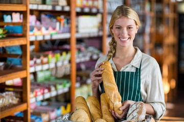 Smiling female staff holding loaf of bread at bread counter