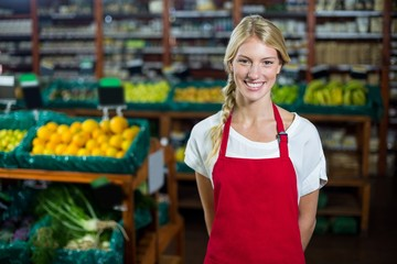 Smiling female staff standing in organic section