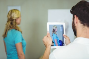 Physiotherapist taking a photograph of a patient
