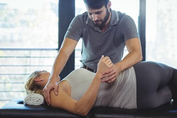 Physiotherapist giving shoulder therapy to a woman