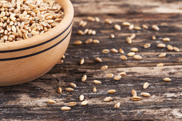 Wooden bowl and wheat grain on wooden background