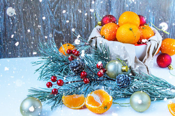 Christmas composition with tangerines, cinnamon and fir twigs in wooden plate on a festive table on a green background with snowflakes and cones fake.tinted