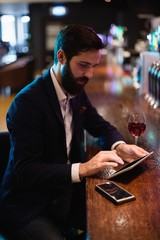 Businessman using digital tablet with wine glass and mobile phon