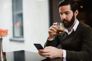 Man having glass of drink while using mobile phone