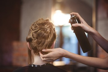 Female hairdresser styling customers hair