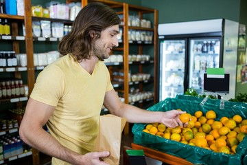 Smiling man selecting oranges in organic section