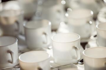 Closeup image of white cups at blurred table background.