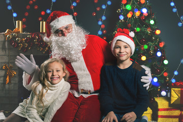 happy Santa Claus and children around the decorated Christmas tree