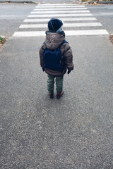 Little boy waiting near a pedestrian crossing