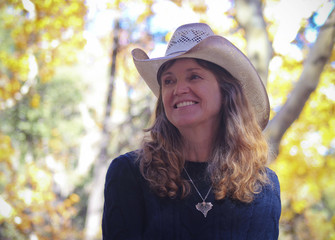 A Cowgirl with Autumn Leaves Behind Her