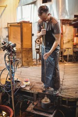 Glassblower using mold to shape a molten glass