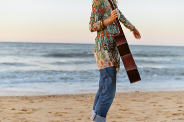 Fragment of a beautiful female playing guitar on the beach, sunset sunny blue sky outdoors background