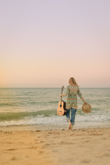 Elegant woman walking on the beach with guitar back view, outdoor background