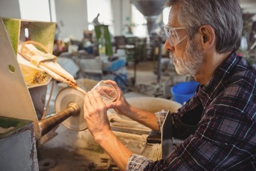 Glassblower polishing and grinding a glassware