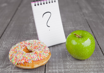 Donut and apple healthy food choices on wooden board