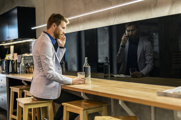 Handsome businessman drinking and talking on the phone