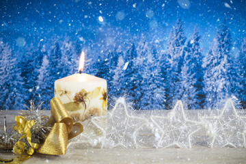 Christmas decoration with candle, golden bow, silver stars, on a blue forest background.