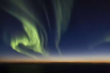 Aurora borealis (Northern Lights) over Arctic Ocean during sunset